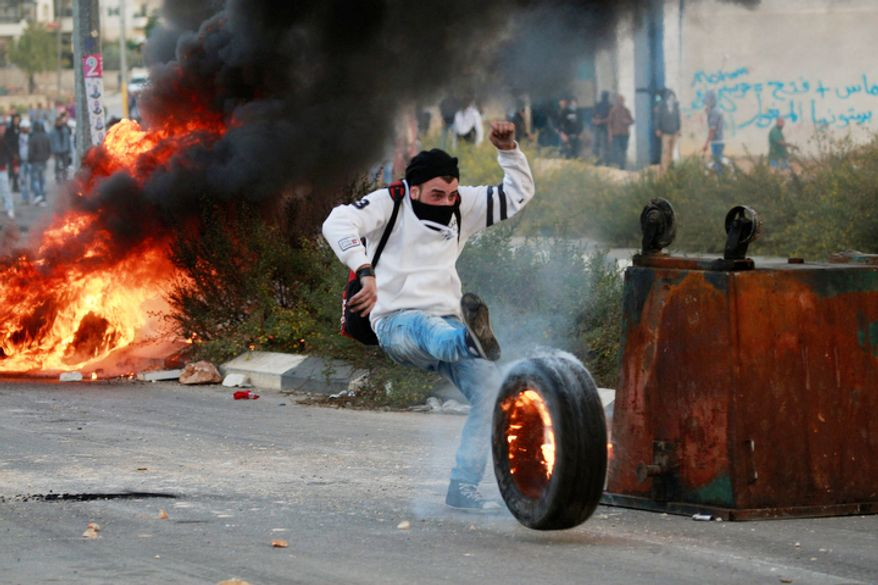 A Palestinian kicks a burning tyre during a protest against Israel's operations in Gaza Strip, outside Ofer, an Israeli military prison near the West Bank city of Ramallah. (AP Photo/Majdi Mohammed)