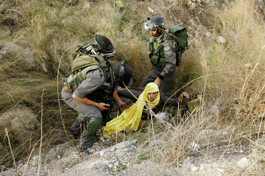 A Palestinian is arrested by Israeli security forces during a protest against the Israeli military operations in Gaza Strip near the West Bank city of Nablus, Sunday, Nov. 18, 2012. (AP Photo/Nasser Ishtayeh)