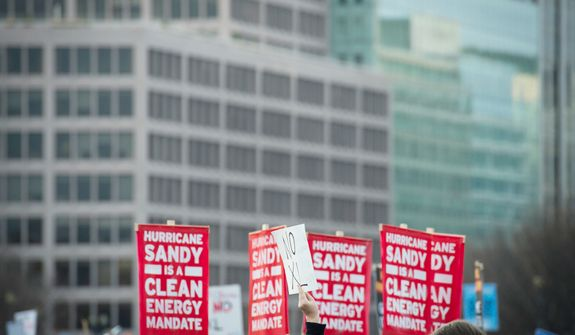 People carry signs against the backdrop of office buildings, during a march to protest the Keystone Pipeline, which began at Freedom Plaza, as it passes by The White House, in Washington, D.C., Sunday, Nov. 18, 2012. (Rod Lamkey Jr./The Washington Times)