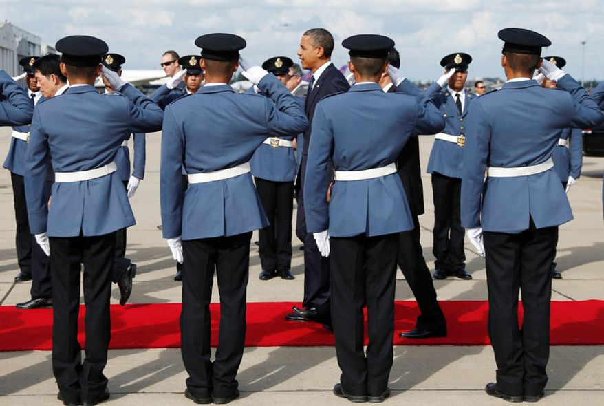 U.S. President Barack Obama, center, walks down a red carpet through saluting military guards of honor as he arrives on Air Force One at Don Mueang International Airport in Bangkok, Thailand. (AP Photo/Carolyn Kaster)