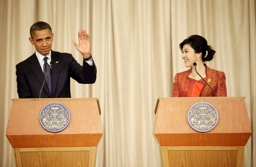 U.S. President Barack Obama, left, waves to members of the media following the conclusion of a joint news conference with Thai Prime Minister Yingluck Shinawatra, right, at Thai Government House in Bangkok, Thailand. (AP Photo/Pablo Martinez Monsivais)