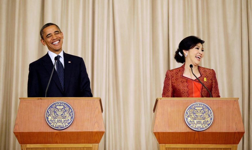 U.S. President Barack Obama, left, reacts when he was asked which was his favorite Thai food, during a joint news conference with Thai Prime Minister Yingluck Shinawatra, right, at Thai Government House in Bangkok, Thailand. (AP Photo/Pablo Martinez Monsivais)