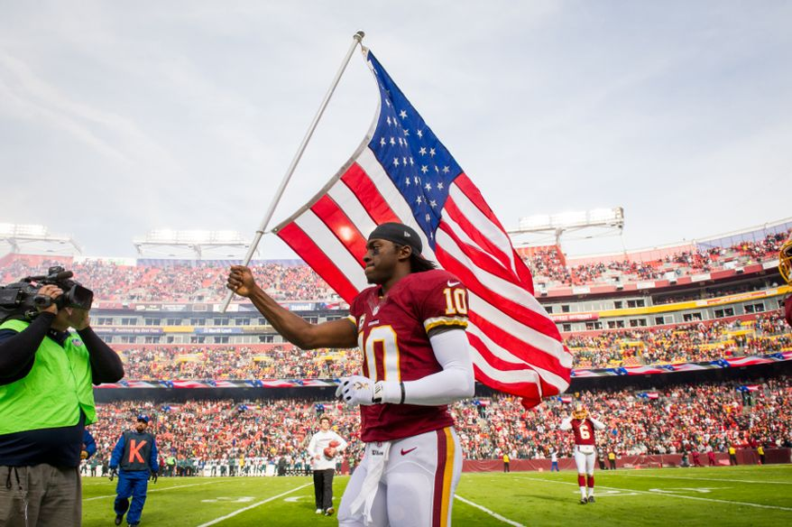 Washington Redskins quarterback Robert Griffin III (10) carries an American flag out on the field for NFL's military salute to service before the the Washington Redskins play the Philadelphia Eagles at FedEx Field, Landover, Md., Sunday, Nov. 18, 2012. (Andrew Harnik/The Washington Times)