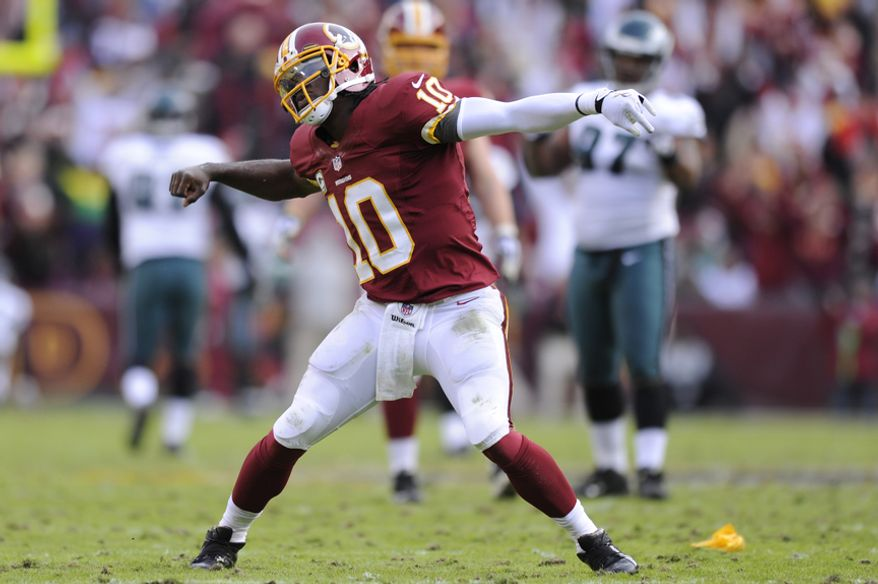 Washington Redskins quarterback Robert Griffin III (10) celebrates his 61-yard touchdown pass to wide receiver Santana Moss in the third quarter at FedEx Field, Landover, Md., Nov. 18, 2012. (Preston Keres/Special to The Washington Times)