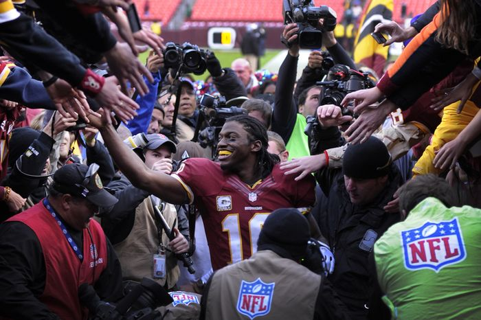 Washington Redskins quarterback Robert Griffin III (10) leaves the field surrounded fans and media after defeating the Eagles 31-6 at FedEx Field, Landover, Md., Nov. 18, 2012. (Preston Keres/Special to The Washington Times)