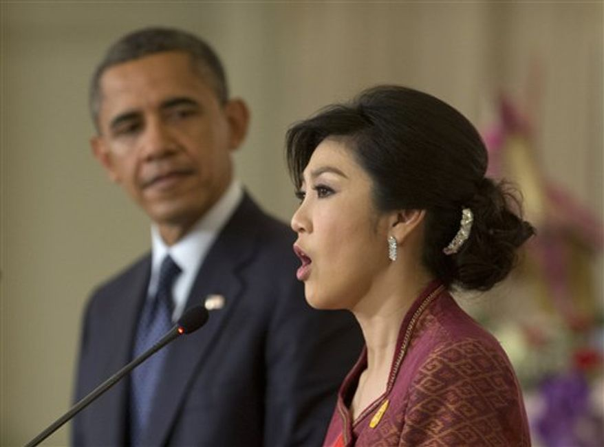 U.S. President Obama looks on from left as Thai Prime Minister Yingluck Shinawatra speaks during a joint news conference at the Government House in Bangkok, Thailand, Sunday, Nov. 18, 2012. (AP Photo/Carolyn Kaster)