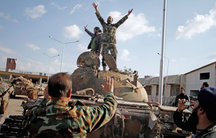Opposition fighters celebrate capturing a tank after storming a military base in Aleppo, Syria, on Monday. Islamist rebels refuse to