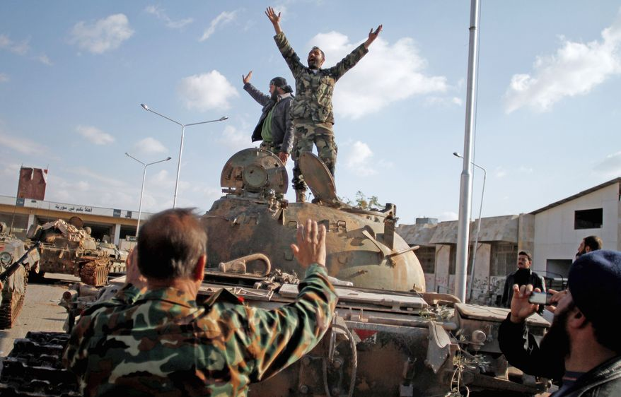 Opposition fighters celebrate capturing a tank after storming a military base in Aleppo, Syria, on Monday. Islamist rebels refuse to join a Western-backed coalition. (Associated Press)