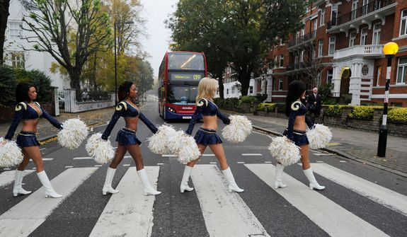 Cheerleaders for the St. Louis Rams NFL team pose for photographs on the Abbey Road zebra crossing made famous by the Beatles in London, Wednesday, Oct. 24, 2012.  The Rams are to play the New England Patriots at Wembley stadium in London, Sunday, Oct. 28 in a regular season NFL game. (AP Photo/Dave Shopland/NFL UK)