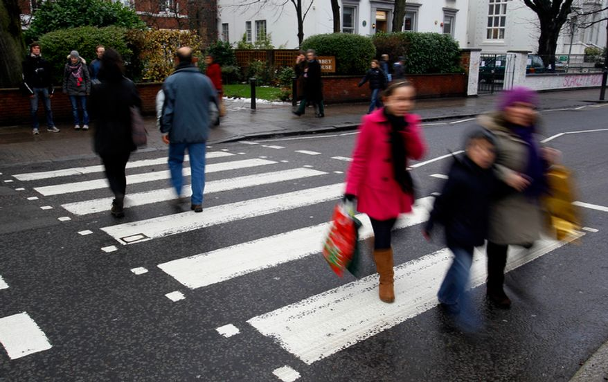 "Tourists cross over the zebra crossing in Abbey Road in London, Wednesday, Dec. 22, 2010. The world-famous zebra crossing which features on the cover of the Beatles' Abbey Road sleeve has been given ""listed"" status by the Government. The crossing - just outside the renowned Abbey Road studios, where the Beatles recorded much of their output - has been given Grade II listing by heritage minister John Penrose. (AP Photo/Kirsty Wigglesworth)"