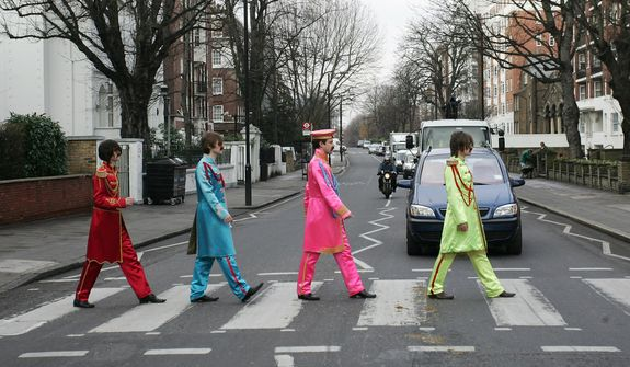 Bonhams Auctioneers staff dressed in Beatles outfits similar to those worn on the cover of their album Sgt. Pepper's Lonely Hearts Club Band, walk across the crossing at Abbey Road in London  to where an announcement was made of the sale of the original lyrics for John Lennon's song ' A Day in the Life'  which appeared as a track on the Sgt. Pepper album, in London Tuesday Jan. 31, 2006. The lyrics are to be sold in a sealed-bid auction concluded on March 7 with an estimated price of 1.5 million,  (US$2.6 million, 2.1 million), London, Tuesday, Jan 31, 2006. (AP Photo/Sang Tan)