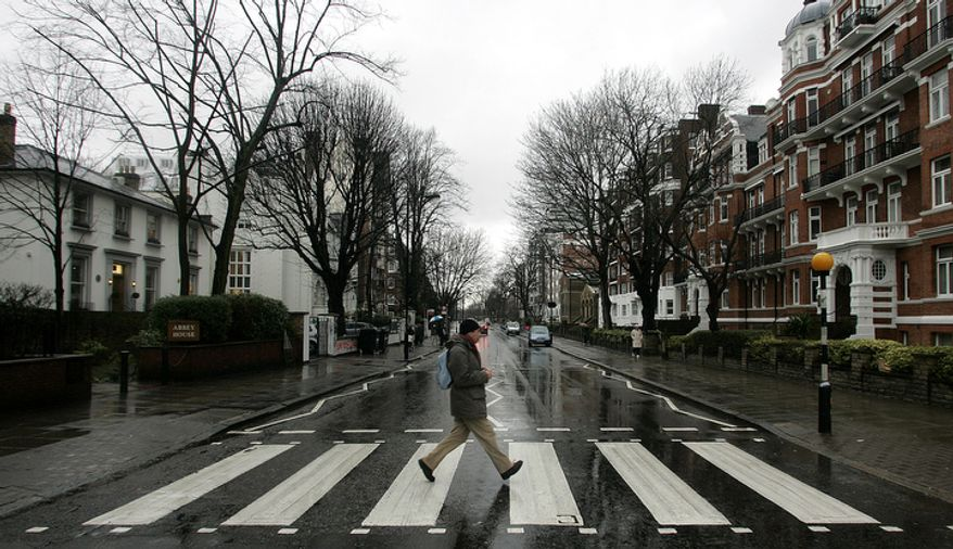 "In this file photo dated Feb. 16, 2010, a man walks across the zebra crossing made famous from the album cover of The Beatles 'Abbey Road' in front of Abbey Road Studios, seen at left, in London. Feb. 16, 2010. Struggling music company EMI Group has shelved plans to sell Abbey Road, the London recording studio made famous by The Beatles. The company now says, Monday Feb. 22, 2010, it wants to keep the facility and is talking to ""interested and appropriate third parties"" about a revitalization project. (AP Photo/Akira Suemori, File)"