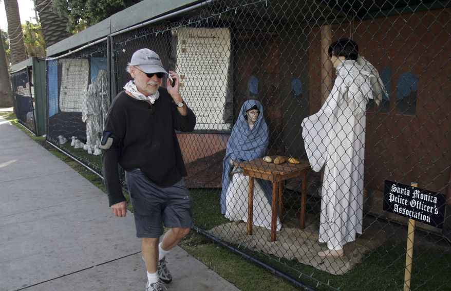 **FILE** A man walks past two of the traditional Nativity scenes along Ocean Avenue at Palisades Park in Santa Monica, Calif., on Dec. 13, 2011. (Associated Press)