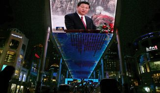 **FILE** A huge screen shows a broadcast of China's new Communist Party General Secretary Xi Jinping speaking in Beijing's Great Hall of the People on Nov. 15, 2012. (Associated Press)