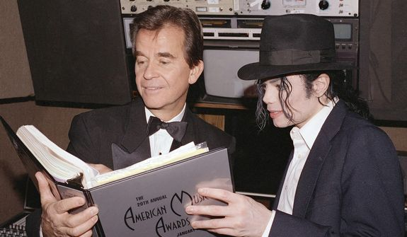 **FILE** Michael Jackson and Dick Clark go over the script during rehearsals for the American Music Awards at the Shrine Auditorium in Los Angeles on Jan. 24, 1993. (Associated Press)