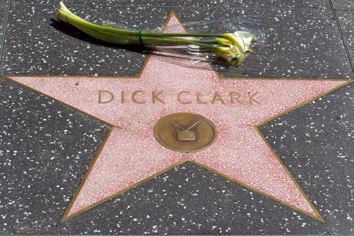 """**FILE** Flowers are left at the star honoring television host Dick Clark on the Walk of Fame in Los Angeles on April 18, 2012. Clark, the television host and entrepreneur who helped bring rock 'n' roll into the mainstream on """"American Bandstand,"""" and later produced and hosted a vast range of programming from game shows to the New Year's Eve countdown from Times Square, died of a heart attack on April 18, 2012. He was 82. (Associated Press)"""