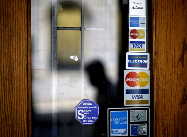 FILE - In this July 18, 2012 file photo, credit card logos are seen on a downtown storefront as a pedestrian passes in Atlanta. Americans cranked up their use of credit cards in the third quarter of 2012, racking up more debt th