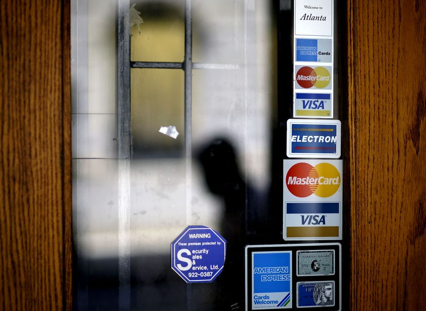 FILE - In this July 18, 2012 file photo, credit card logos are seen on a downtown storefront as a pedestrian passes in Atlanta. Americans cranked up their use of credit cards in the third quarter of 2012, racking up more debt than a year ago, while also being less diligent about making payments on time, an analysis of consumer-credit data shows. (AP Photo/David Goldman, File)