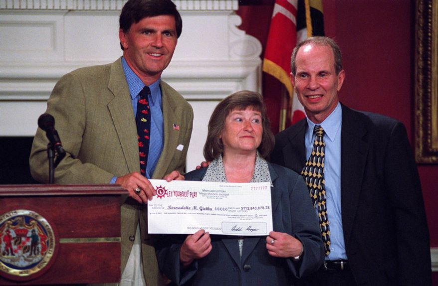 "**FILE** Bernadette ""Bernie"" Gietka (center), winner of the $112 million interstate Mega Millions lottery, holds her winnings check at the Maryland State House in Annapolis with Maryland Gov. Robert L. Erlich (left) and Maryland Lottery Agency Director Buddy Roogow on July 2, 2003. (Caroling Lee/The Washington Times)"