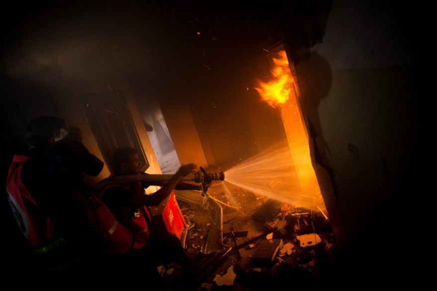 Palestinians firefighters try to extinguish a fire after an Israeli strike on a building of Gaza City, Monday, Nov. 19, 2012. Palestinian militant group Islamic Jihad says an Israeli strike on a Gaza media center has killed one of its top militant leaders. (AP Photo/Bernat Armangue)