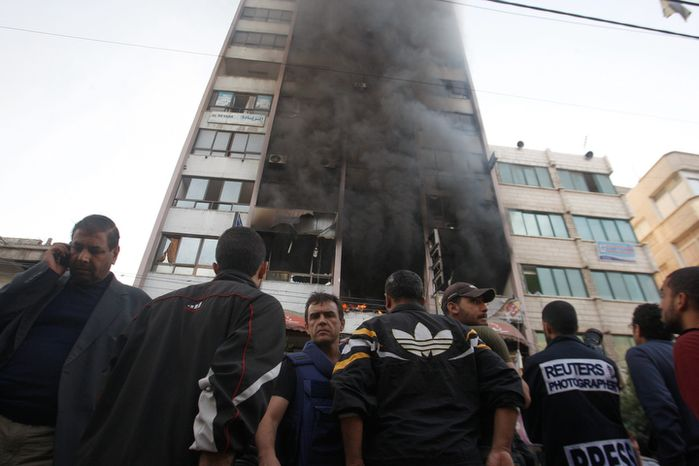 People stand in front of a high rise housing media organizations in Gaza City, Monday, Nov. 19, 2012. Israeli military struck the building for the second time in two