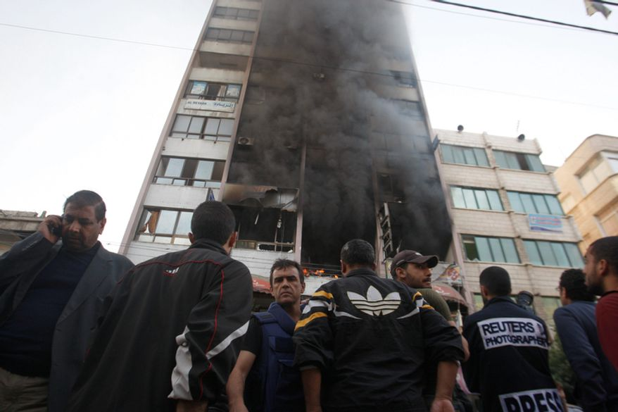 People stand in front of a high rise housing media organizations in Gaza City, Monday, Nov. 19, 2012. Israeli military struck the building for the second time in two days. The Hamas TV station, Al Aqsa, is located on the top floor. (AP Photo/Hatem Moussa)