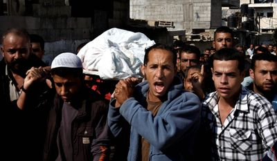 Palestinian mourners carry the body of farmer Rashed Abu Amra, 45, during his funeral in Deir Al Balah, central Gaza Strip, Monday, Nov. 19, 2012. The Palestinian civilian death toll mounted Monday as Israeli aircraft struck densely populated areas in the Gaza Strip in its campaign to quell militant rocket fire menacing nearly half of Israel's population. (AP Photo/Adel Hana)