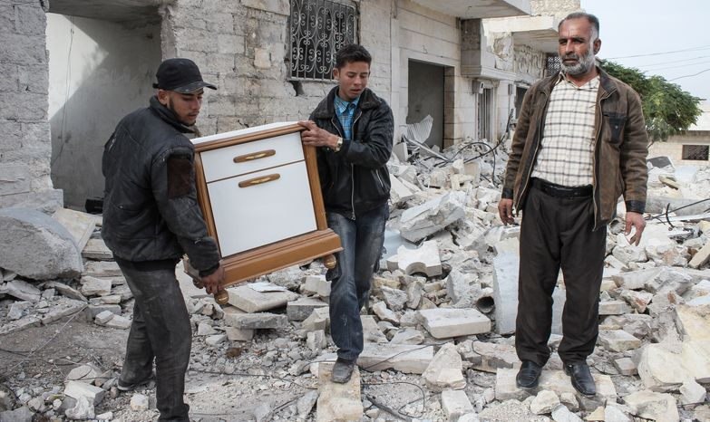 **FILE** A Syrian father and two of his sons salvage furniture from their home in Maraat al-Numan, Syria, on Nov. 17, 2012. The house was destroyed in bombing by gov
