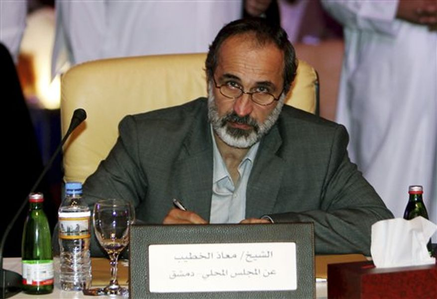 Islamic preacher Maath al-Khatib poses for a photo after being elected president of the newly formed Syrian National Coalition for Opposition and Revolutionary Forces, created after the Syrian National Council (SNC) agreed to the new group, on Sunday, Nov. 11, 2012. (AP Photo/Osama Faisal)