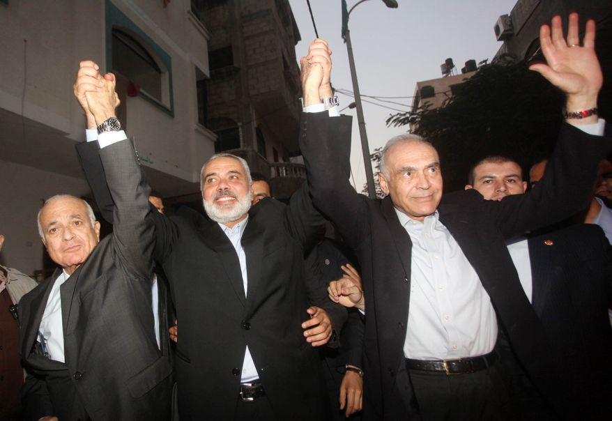 Arab League Secretary General Nabil Elaraby, Hamas Prime Minister Ismail Haniyeh and Egyptian Foreign Minister Mohammed Kamel Amr unite with the people Tin Gaza City on Tuesday. World leaders traveled to the region on a truce mission. (Associated Press)