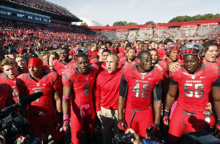 FILE - This Oct. 13, 2012 file photo shows Rutgers head coach Kyle Flood, center, standing with his players as they sing Rutgers' Alma Mater after defeating Syracuse 23- 15 in an NCAA college football game at High Points Solutions stadium in Piscataway, N.J. Rutgers is announcing that it will join the Big Ten at an afternoon news conference Tuesday, Nov. 20, 2012,  on its campus in Piscataway, N.J. (AP Photo/Mel Evans, File)