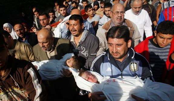 Palestinian mourners carry the bodies of Foud Hijazi, 45, and his sons Suhaib, 2, and Mohammed, 4, all of whom were killed in an Israeli strike, during their funeral in the Jebaliya refugee camp in Gaza Strip on Nov. 20, 2012. (Associated Press)