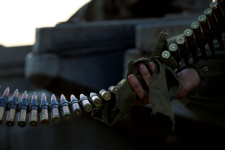An Israeli soldier cleans ammunition as he sits on top of a tank in a staging area near the Gaza border in southern Israel on Nov. 20, 2012. Israeli aircraft battered the headquarters of the Islamic National Bank, which Gaza's Hamas leaders set up to sidestep international sanctions on their rule. (Associated Press)