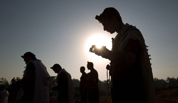 Israeli soldiers read from a holy book as they pray in a staging area near the Gaza border in southern Israel on Nov. 20, 2012. Israeli aircraft battered the headquarters of the Islamic National Bank, which Gaza's Hamas leaders set up to sidestep international sanctions on their rule. (Associated Press)