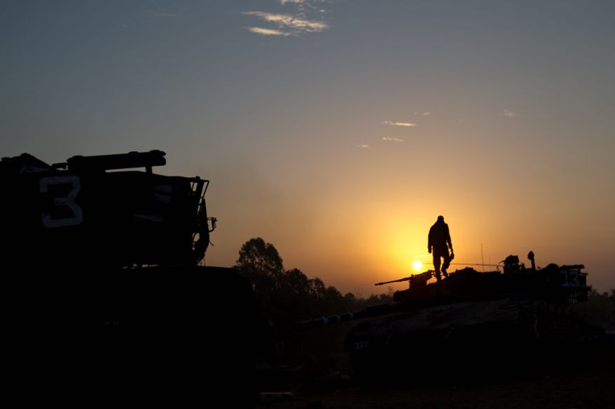 An Israeli soldier stands atop a military vehicle as the sun rises in a staging area near the Gaza border in southern Israel on Nov. 20, 2012. Israeli aircraft battered the headquarters of the Islamic National Bank, which Gaza's Hamas leaders set up to sidestep international sanctions on their rule. (Associated Press)