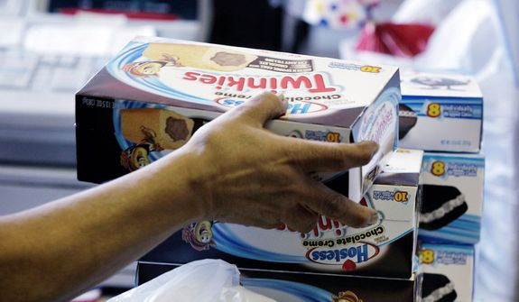 A cashier rings up boxes of Hostess Twinkies and Cup Cakes at the Hostess Brands' bakery in Denver on Nov. 16, 2012. (Associated Press)
