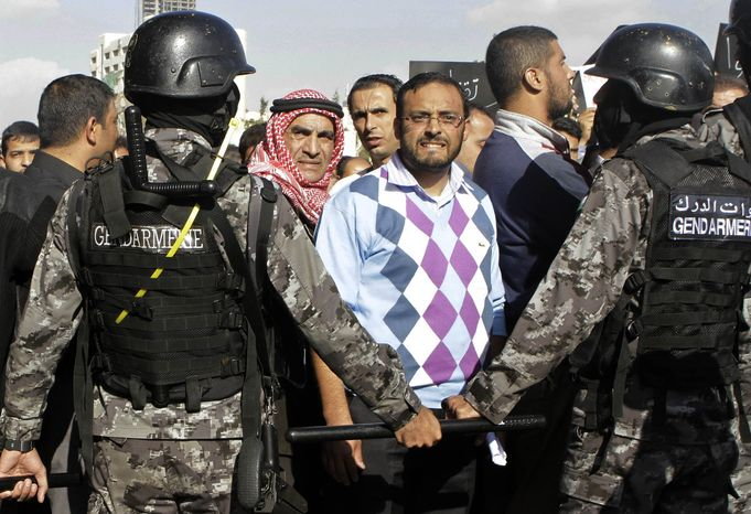 Jordanian police stand guard during a protest against the government's decision to raise prices for subsidized fuel in Amman, Jordan, on Nov. 19, 2012. Nearly a week after the announcement, which sparked unrest that left one person dead and scores wounded, protests across the country continued. The protests have included rare demands for King Abdullah II to be deposed. (Associated Press)