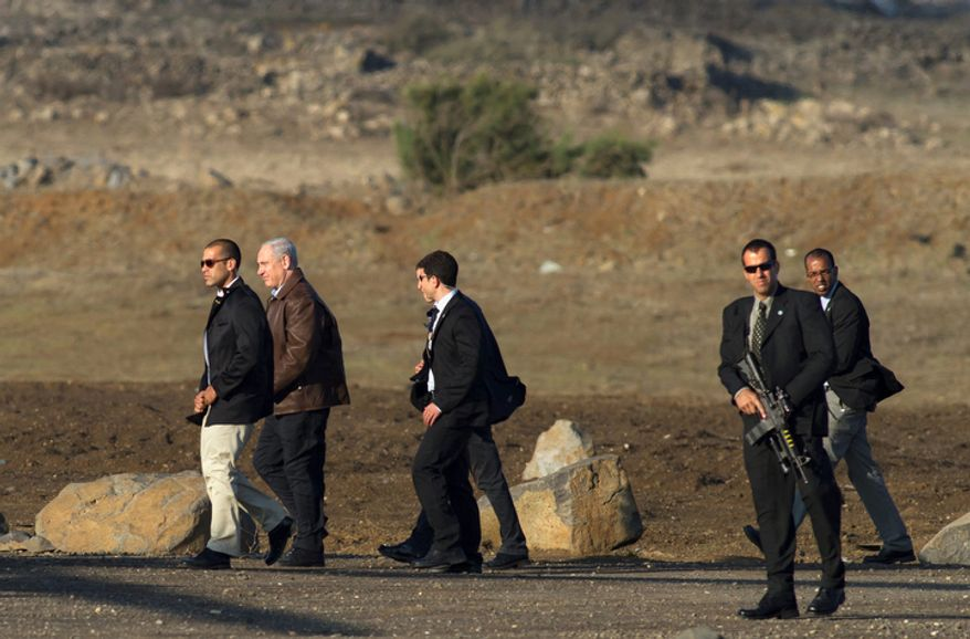 **FILE** Israeli Prime Minister Benjamin Netanyahu (second left) is surrounded by bodyguards as he walks towards a military helicopter following a visit to the Golan Heights on Nov. 14, 2012. (Associated Press)