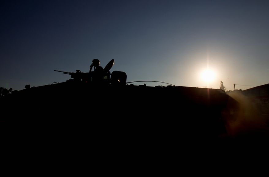 **FILE** Israeli soldiers stand on an armored personnel carrier close to the Gaza border in Israel on Nov. 15, 2012. (Associated Press)