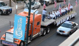 **FILE** A flatbed truck carries wounded veterans and their families during a parade on Nov. 15, 2012, in Midland, Texas, before it was struck by a train. Four veterans were killed and sixteen people injured in the resulting collision. (Associated Press/Reporter-Telegram, James Durbin)