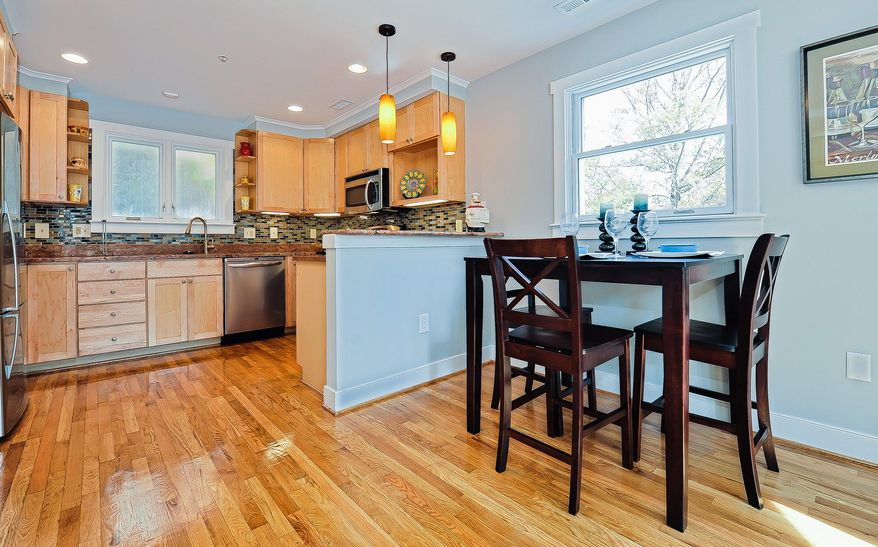 The kitchen has stainless steel appliances, granite counters and a glass tile backsplash.