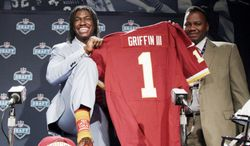 Baylor quarterback Robert Griffin III, left, is joined by his father Robert Griffin Jr. as he displays his sock and new jersey while speaking to reporters after he was selected as the second pick overall by the Washington Redskins in the first round of the NFL football draft at Radio City Music Hall, Thursday, April 26, 2012, in New York. (AP Photo/Mary Altaffer)