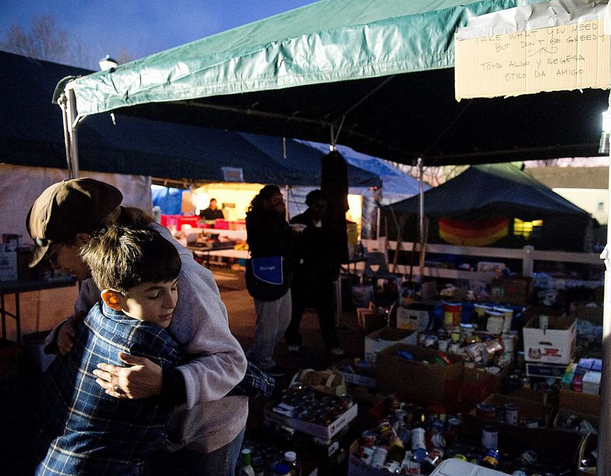 Andrew hugs volunteer Amy Sahlin at a relief station in Union Beach, N.J. on Wednesday. He and his family will volunteer at the station Thanksgiving Day. (Barbara L. Salisbury/The Washington Times)