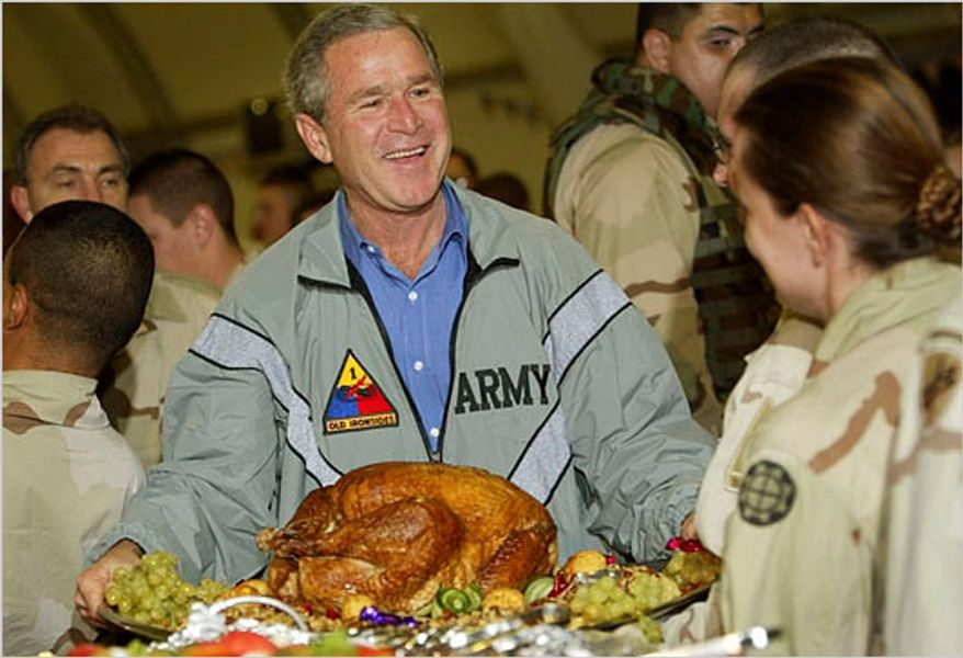 A presidential Thanksgiving past: President George W. Bush prepares to serve dinner to U.S. troops in Baghdad after paying a surprise Thanksgiving Day visit  to Iraq in 2003. (AP Photo/Pablo Martinez Monsivais)