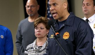 ** FILE ** In this Oct. 29, 2012, photo, Newark Mayor Cory Booker, right, speaks during a news conference at the Office of Emergency Management in Newark, N.J. Booker says he plans to honor a Twitter challenge and live on food stamps for at least a week. In a Twitter exchange Sunday, Nov. 18, 2012, Booker and a user named TwitWit discussed government funding for school meals. Booker suggested they both try living on food stamps for a week or month. (Associated Press)