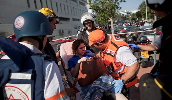 Israeli rescue workers and paramedics carry an injured woman  from the site of a bombing in Tel Aviv, Israel, Wednesday, Nov. 21, 2012. A bomb ripped through an Israeli bus near the nation's military headquarters in Tel Aviv on Wednesday, wounding several people, Israeli officials said. The blast came amid a weeklong Israeli offensive against Palestinian militants in Gaza that has killed more than 130 Palestinians. (AP Photo/Oded Balilty)
