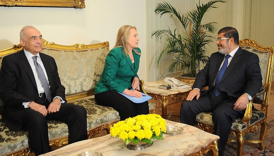 """In this photo released by the Egyptian Presidency, U.S. Secretary of State Hillary Rodham Clinton, center, meets with Egyptian President Mohammed Morsi, right, and Egyptian Foreign Minister Mohammed Kamel Amr, left, in Cairo, Egypt, Wednesday, Nov. 21, 2012. Secretary of State Hillary Rodham Clinton has arrived in Cairo in her diplomatic push to forge a truce between Israel and Gaza rulers of Hamas. Her visit comes hours after a bomb exploded on an Israeli bus in Tel Aviv, wounding several. Clinton is looking to piece together a deal to end Israel's weeklong offensive in the Gaza Strip. Clinton said the U.S. """"strongly condemns"""" today's bus bombing, calling it a """"terrorist attack."""" (AP Photo/Egyptian Presidency)"""