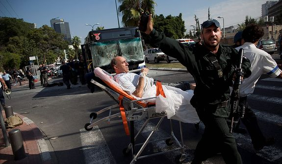 Israeli rescue workers and paramedics carry a wounded person from the site of a bombing in Tel Aviv, Israel, Wednesday, Nov. 21, 2012. A bomb ripped through an Israeli bus near the nation's military headquarters in Tel Aviv on Wednesday, wounding several people, Israeli officials said. (AP Photo/Oded Balilty)