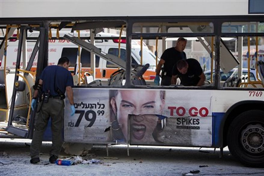 Israeli police officers examine a blown-up bus at the site of a bombing in Tel Aviv, Israel, Wednesday, Nov. 21, 2012. (AP Photo/Oded Balilty)