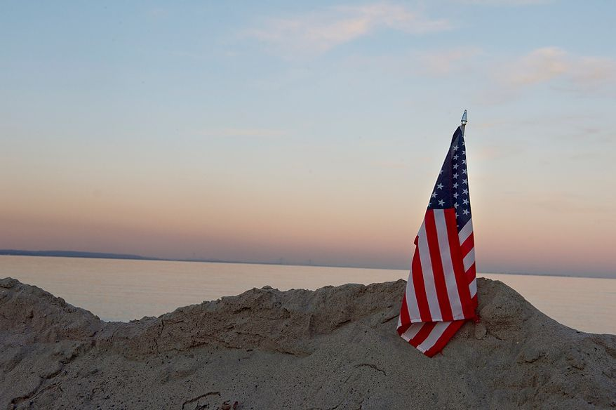 An American flag has been stuck in one of the huge sand dunes in Union Beach, N.J. on Wednesday, Nov. 21, 2012. The Audas family has donated items here that they collected in Project Keep Them Cozy, which Abbi, 12, and Andrew, 9, spearheaded. The family is spending their Thanksgiving up here volunteering. (Barbara L. Salisbury/The Washington Times)